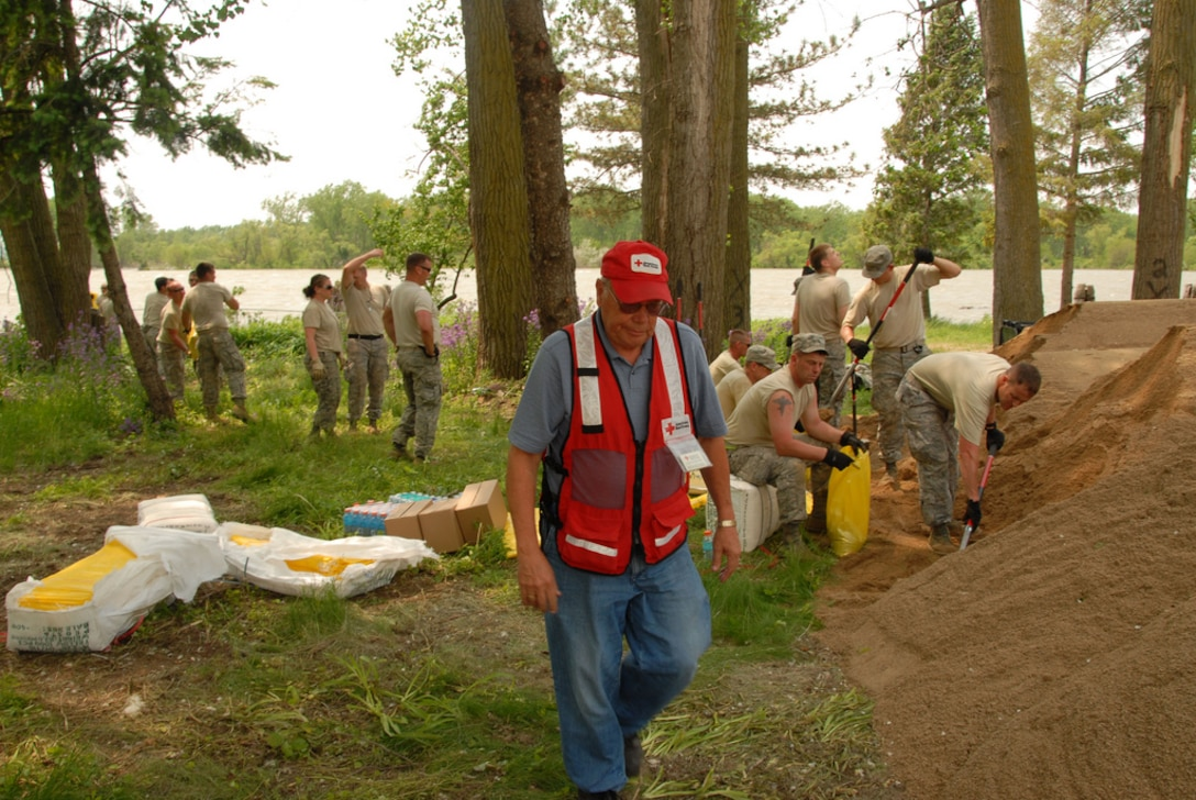 DAKOTA DUNES, S.D. - Red Cross volunteers are present at the Dakota Dunes levee project providing water and snacks to help keep South Dakota National Guard members and civilian volunteers hydrated and full of energy to aid in flood response efforts along the Missouri River, Thursday, June 2, 2011.  Soldiers and Airmen are working around the clock in this historic flooding event and continue to work side by side with local, state and federal agencies and volunteers to provide flooding assistance to the citizens of South Dakota.  (SDNG photo by Tech. Sgt. Quinton Young) (RELEASED)