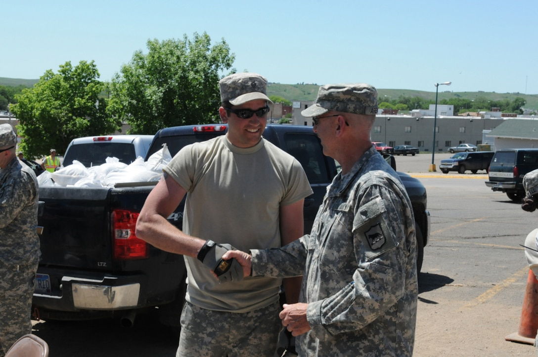 South Dakota Army National Guard Command Sgt. Maj. George Arends (right), serving with Task Force 147, checks on the morale of Specialist Derek Austin and his fellow troops from the 842nd Engineering Company working on sandbagging efforts, Friday, June 3, 2011.  More than 1,150 Soldiers and Airmen of the South Dakota National Guard are currently on duty to help South Dakota citizens during this historic flood event occurring along the Missouri River. (SDNG photo by Master Sgt. Christopher Stewart) (RELEASED)