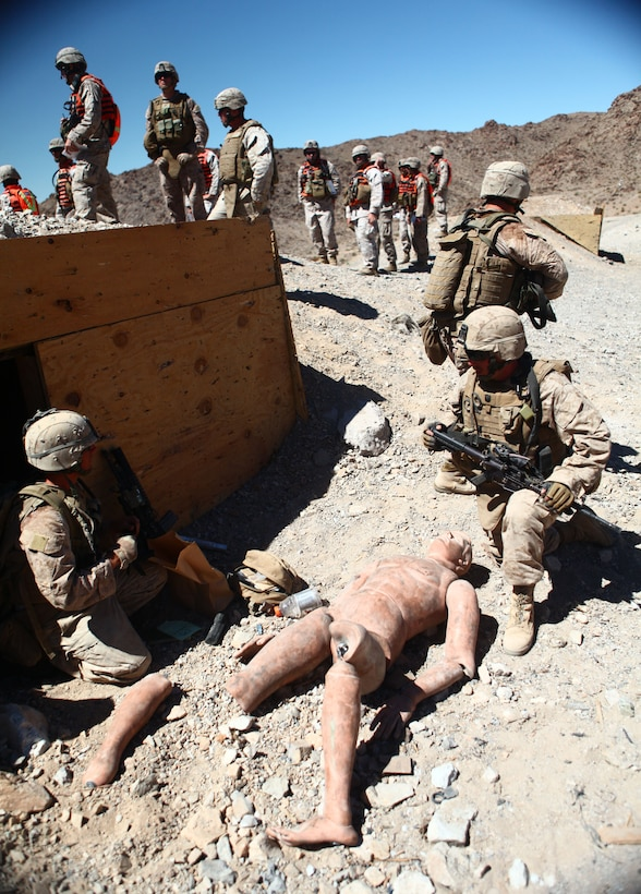 Marines with Company B, 1st Battalion, 6th Marine Regiment, 2nd Marine Division, gather sensitive material from a simulated enemy combatant during the Range 400 training exercise aboard Marine Corps Base 29 Palms, Calif., June 6, 2011. The event was part of the Enhanced Mojave Viper predeployment training evolution and required those involved to coordinate extensively with one another while advancing on their objectives.