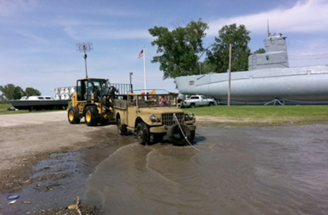 Larry Simbro and Michael Wangberg move items out of oncoming flood waters at Freedom Park here June 1, 2011, in Omaha, Neb. Freedom Park is an outdoor museum that features numerous military exhibits and has been overcome by rising waters of the Missouri River. Members of Offutt Air Force Base moved museum artifacts to higher ground until the flood waters recede. Mr. Simbro and Mr. Wangberg are heavy equipment operators with the 55th Logistics Readiness Squadron. (U.S. Air Force photo/Maj. Melvin Maxwell)