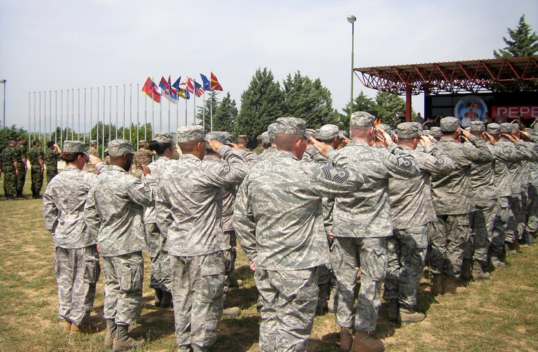CAMP PEPELISHTE, Macedonia -- Members of the United States Air Force and Army salute during the Macedonian and American National Anthems at the opening ceremony of Medical Training Exercise in Central and Eastern Europe 2011 here June 6.  The countries participating in this year's MEDCEUR are Macedonia, Montenegro, Bosnia and Herzegovina, Serbia, Slovenia, Norway and the United States.  MEDCEUR is a Partnership for Peace and chairman of the Joint Chiefs of Staff-sponsored regional and multilateral exercise in Central and Eastern Europe designed to provide medical training and operational experience in a deployed environment.  (U.S. Air Force photo/Master Sgt. Kelley J. Stewart)