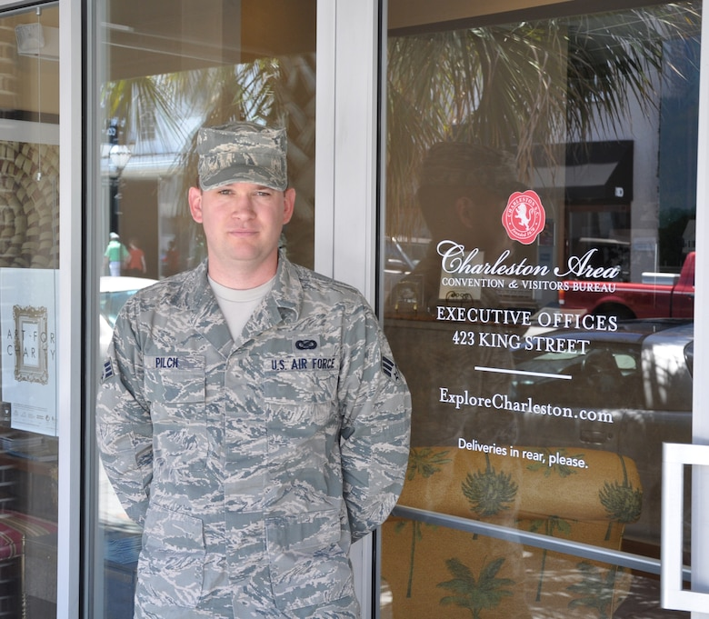 Senior Airman Bobby Pilch, a reservist with the 315th Airlift Wing Public Affairs stands by the entrance to his civilian employer, the Charleston Area Convention and Visitors Bureau. (U.S. Air Force Photo/Kevin McManus)