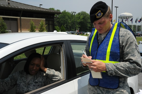 Staff Sgt. Daniel Hadley, 11th Security Forces Squadron crime prevention NCO, simulates writing a ticket for Senior Airman Desantis C. Symonette, 11 SFS Visitor Control Center security clerk during a seatbelt and cell phone selective enforcement check May 26. (U.S. Air Force photo by Airman 1st Class Bahja J Jones)