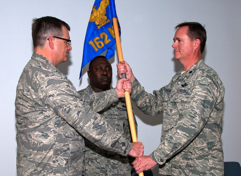 Col. Mick McGuire, left, 162nd Fighter Wing commander, passes the 162nd Mission Support Group flag to Lt. Col. Garry Beauregard as a symbol of his assumption of command June 4. The group consists of about 400 Airmen who support the international F-16 pilot training mission at Tucson International Airport. (U.S. Air Force photo/Master Sgt. Dave Neve)
