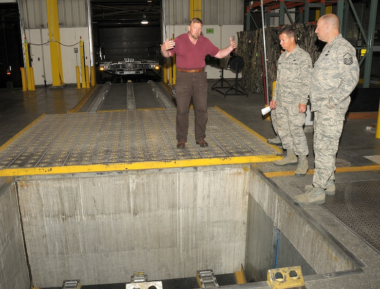 Mr, Charles Carr, Weight Supevisor 7 in Air Terminal Operations, conducts a tour of the terminal warehouse facility for Master Sergeant Burt Sherring and Airman First Class Jesse Kramer from the Air Terminal Operations Squadron, 146th Airlift Wing, Channel Islands Air National Guard Station, Calif.  on June 6, 2011. Mr. Carr briefed the members on the various equipment available to them as well as safety protocol.  The 146th AW sent three squadrons to Joint Base Elmendorf-Richardson, Anchorage, Alaska on Saturday, June 4, 2011. The Air Terminal Operations Squadron, Logistics Readiness Squadron, and the Security Force Squadron moved down range to complete there respective annual training requirements.(Photo by Tech. Sgt. Alex Koenig)