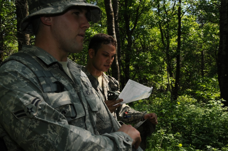 Staff Sergeant Mitch Pitoscia and Airman 1st Class Corey Pitoscia, members of the Security Forces Squadron, 148th Fighter Wing, Duluth, Minn., consult their map and compass as they make their way through the land navigation course at Camp Ripley, Minn. on June 5, 2011.  The land navigation course tests the ability to plot out a course prior to entering the woods, but also the ability to stay on that course despite difficult terrain.  (U.S. Air Force Photo by Tech. Sgt. Scott Herrington)