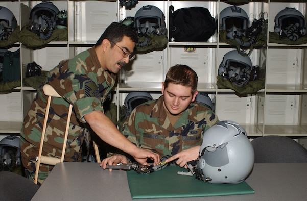 Master Sgt. Bob Barajas (left), trains Senior Airman Zachery Lange on the intricasies of aircrew lifesupport equipment.