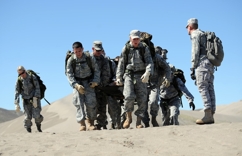 BRUNEAU STATE PARK, Idaho – A team of Airmen from the 726th Air Control Squadron carry a 200-pound dummy to the top of a sand dune while completing a 1.5-mile course during a training exercise at Bruneau State Park June 3. This team-building exercise helps the 726th ACS to maintain a combat ready status in order to provide air battle management to joint air, land and sea power at a moment's notice. (U.S. Air Force photo by Senior Airman Debbie Lockhart)