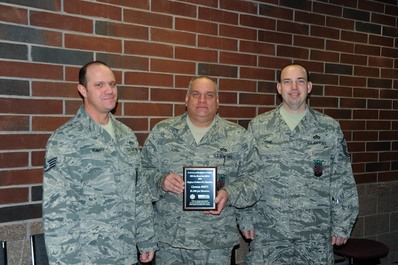 """Staff Sgts. Robert Hunt, Marshal Holt and Master Sgt. Ryan York show the award that the Gowen Field Fire Department received from the Muscular Dystrophy Association this by the Professional Firefighters of Idaho. The award was given on behalf of the MDA for the most dollars raised per member during the 2010 """"Fill the Boot"""" event."""