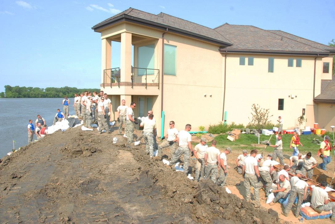 DAKOTA DUNES, S.D. - A wall unlike any other.  Airmen from the 114th Fighter Wing, Sioux Falls SD, finish a section of levee in the Bay Hill area of Dakota Dunes June 5.  The levees that Soldiers and Airmen have built with the joint effort of civilian contractors, civilian volunteers and several local, state and federal agencies, will require security and patrolling efforts.  The 114th Fighter wing has been tasked with levee patrol and perform 24/7 patrols of the 3.8 mile stretch of levee along the shores of the Missouri River. (SDNG photo by Tech. Sgt. Quinton Young)(RELEASED)