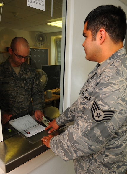SPANGDAHLEM AIR BASE, Germany – Second Lt. Adam Wenke, left, 52nd Comptroller Squadron deputy disbursing officer, accepts a return deposit for a voucher loan from Staff Sgt. Johann Barco, 52nd Comptroller Squadron alternate deputy disbursing officer, at the cashier cage here June 9. The cashier cage services the base's Airmen and families by funding vouchers, loans and other financial needs for the Spangdahlem Air Base community. (U.S. Air Force photo/Airman 1st Class Dillon Davis)