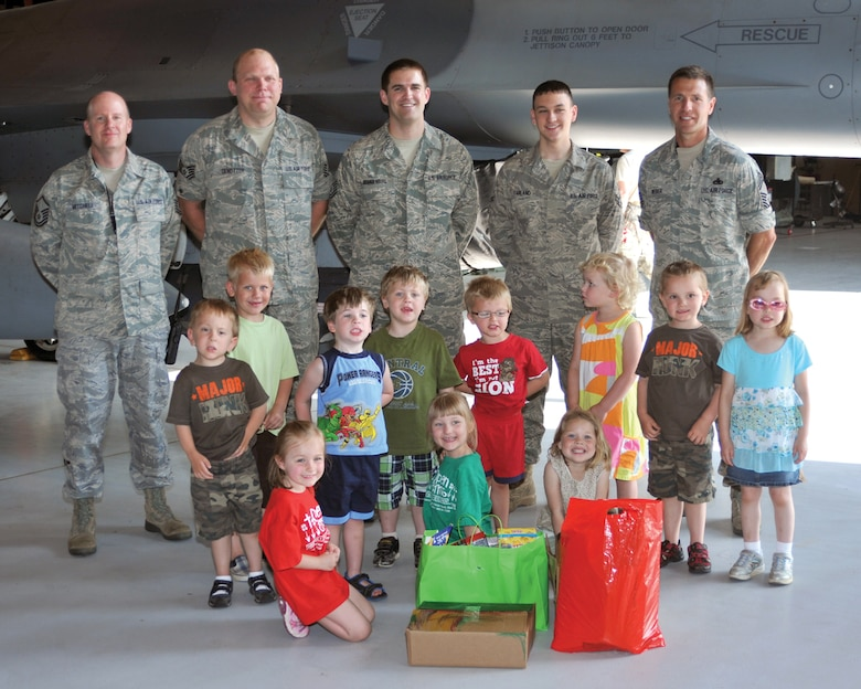 Members of the South Dakota Air National Guard are photographed with children from the Open Arms Christian Child Care Center at Joe Foss Field June 7.  The children visited the base to distribute care package they put together for the deployed members of the unit.  (Air Force photo by Master Sgt. Nancy Ausland)(RELEASED)