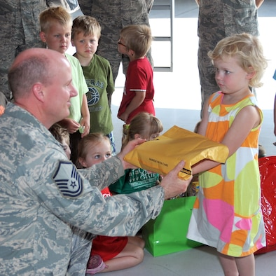 Master Sgt. Thomas Mitchell, 114th Maintenance Squadron, recieves a care package from Rowan Alberts at Joe Foss Field, S.D. June 7.  Rowan and other children from the Open Arms Christian Child Center visited the base to distribute care packages they put together for deployed members. (Air Force photo by Master Sgt. Nancy Ausland)(RELEASED)