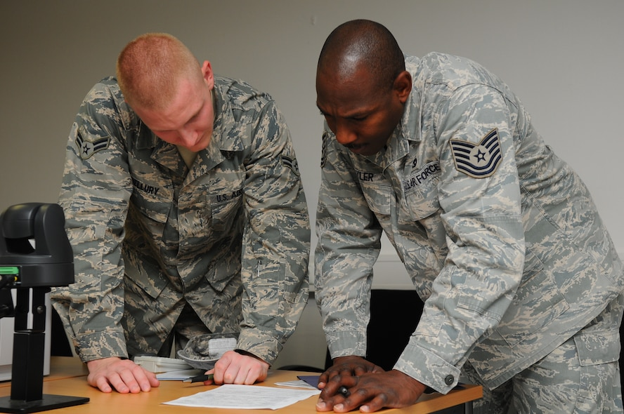 SPANGDAHLEM AIR BASE, Germany – Airman 1st Class Michael Bellury, 52nd Force Support Squadron customer support journeyman, helps Tech. Sgt. Eric Hyler, 52nd Logistics Readiness Squadron customer support supervisor, verify a form before signing it at First Stop here June 6. First Stop is the initial inprocessing center where Airmen and dependants acquire the necessary documents and information to live and work at their new duty station. (U.S.  Air Force photo/Airman 1st Class Dillon Davis
