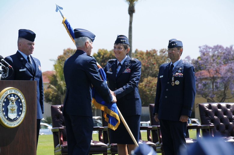 Lieutenant Gen. Ellen Pawlikowski, the first female Space and Missile System Center commander, accepts the command flag from Air Force Space Command commander, Gen. William Shelton, as SMC Command Chief Master Sgt. Mark Repp (far left) and outgoing SMC commander, Lt. Gen. Tom Sheridan (far right) look on.  General Shelton officiated the change of command ceremony held on Fort MacArthur's parade grounds, June 3. (Photo by Joe Juarez)