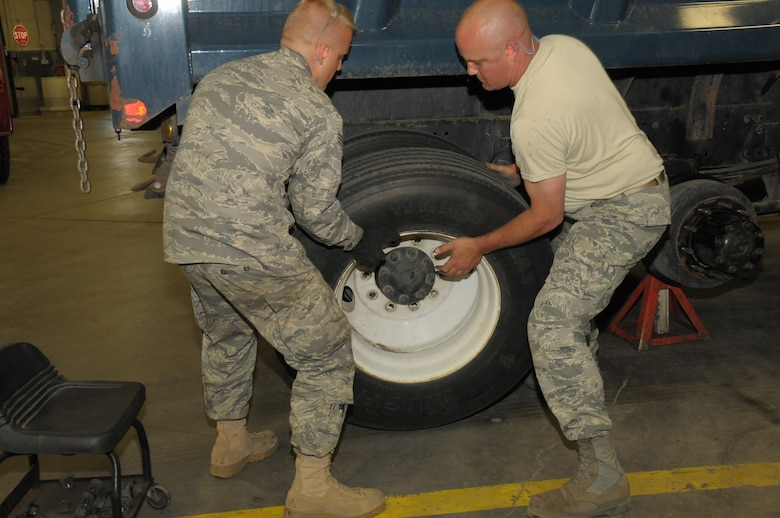 Senior Airman Tobias Burrier and Staff Sergeant Jeffery Strong from Vehicle Maintenance, 146th Logistics Readiness Squadron, 146th Airlift Wing, Channel Islands Air National Guard Station, Calif. work together to remove a tire from a five-ton truck during an annual training deployment to Joint Base Elmendorf-Richardson, Anchorage, Alaska on June 8, 2011. The Air Terminal Operations Squadron, Logistics Readiness Squadron,and the Security Forces Squadron, from the 146AW, traveled to Alaska to complete their respective annual training requiremens. (Photo by Tech. Sgt. Alex Koenig)