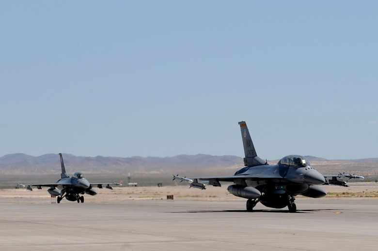 NELLIS AIR FORCE BASE, Nev.-- A two-ship of F-16 Fighting Falcons assigned the U.S. Air Force Weapons School taxi out to the Nellis flightline during the Mission Employment phase, June 8, 2011. More than 5,000 personnel are involved in the final phase of the Weapons School graduate course, resulting in 89 students from 21 separate combat specialties graduating as U.S. Air Force Weapons Officers.(U.S. Air Force photo by Staff Sgt. Taylor Worley)