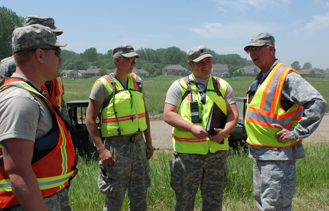 DAKOTA DUNES, S.D. - Brig. Gen. Wayne Shanks, assistant adjutant general of the South Dakota Air National Guard, takes a few moments to visit with Soldiers of the 211th Engineer Company, who are conducting levee patrols at Dakota Dunes on June 8. Soldiers and Airmen with South Dakota National Guard are transitioning from sandbagging operations to a levee patrol mission on the Dakota Dunes levee system. (SDNG photo by Sgt. Charlie Jacobson)(RELEASED)
