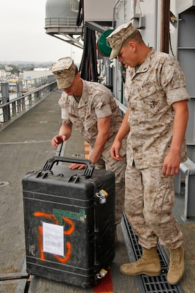 Lance Cpls. Miles G. Norris and Derek M. Sikes, field radio operators, communications section, 15th Marine Expeditionary Unit (MEU), load communications equipment on to the USS Peleliu for the STRAPEX they will be conducting this week, June 10. The STRAPEX or strap exercise is designed to better familiarize the 15th MEU communications Marines with their equipment.