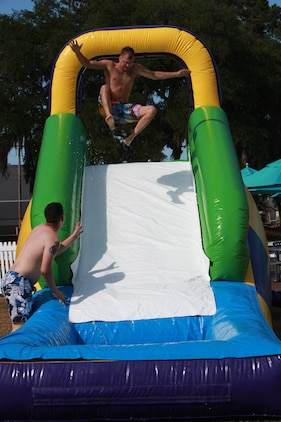 Lance Cpl. Jacom Denson, a Marine Fighter Attack Squadron 115 airframes mechanic, jumps onto the water slide outside of Afterburners June 11 during a cookout for the 101 Days of Summer Drug and Alcohol-Free Challenge.::r::::n::