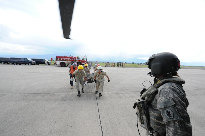 Honduran firefighters bring a litter to a waiting UH60 helicopter during an exercise June 7, 2011, at Soto Cano Air Base, Honduras. The exercise, called Central America Sharing Mutual Operational Knowledge and Experiences, or CENTAM SMOKE, allows U.S. and Honduran firefighters four days of team-building training.