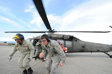 """Ruben Barahona, a Honduran firefighter, and Senior Airmen Christopher Benner, 612th Air Base Squadron firefighter, carry away a life-sized 175-pound """"victim"""" from a UH60 helicopter during an exercise June 7, 2011 at Soto Cano Air Base, Honduras. The exercise, called Central America Sharing Mutual Operational Knowledge and Experiences, or CENTAM SMOKE, allows U.S. and Honduran Airmen and civilian firefighters four days of team-building training."""