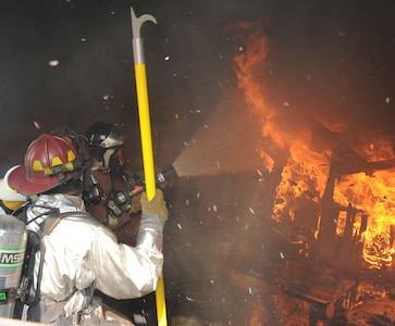 Staff Sgt. Justin Talbot, (left) 612th Air Base Squadron firefighter, coaches Hector Cordova, Honduran firefighter, at a controlled structure fire during an exercise June 8, 2011, at Soto Cano Air Base, Honduras. The exercise, called Central America Sharing Mutual Operational Knowledge and Experiences, or CENTAM SMOKE, allows U.S. and Honduran Airmen and civilian firefighters four days of team-building training.