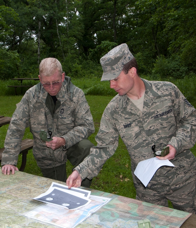 Chief Master Sgt. Dave C. Coldren a Flight Engineer with the 109th Airlift Squadron, Minnesota Air National Guard looks on as Tech. Sgt. Steven P. Best conducts compass usage and mapping at Afton State Park, Hastings Minn. June 11, 2011. Sixty-two members of the 133rd Airlift Wing, Minnesota Air National Guard are taking part in their annual survival training at Afton State Park, Hastings Minn. including survival equipment, lift raft familiarization, parachute disentanglement and rescue techniques. U.S. Air Force Photo by Tech. Sgt. Erik Gudmundson (released)