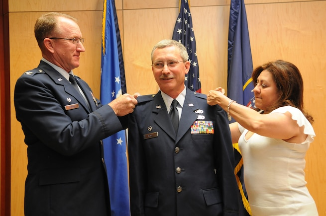 Lt. Col. Jack Wall, 151st Mission Support Group commander, is pinned to the rank of colonel during his promotion ceremony by Col. Samuel Ramsey, 151st Air Refueling Wing commander, and his wife Doreen. Photo by Tech. Sgt. Jeremy Giacoletto-Stegall. (RELEASED)