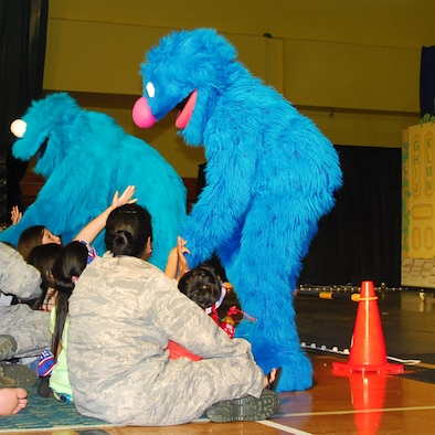 Muppets, Cookie Monster and Grover, greet audience members at a performance during a performance at the Youth Center gym here June 9. The United Service Organizations teamed with Sesame Workshop, the non-profit organization that produces Sesame Street, to bring The Sesame Street/USO Experience for Military Families to the Asia-Pacific region.(U.S. Air Force photo/Airman 1st Class Whitney Tucker)