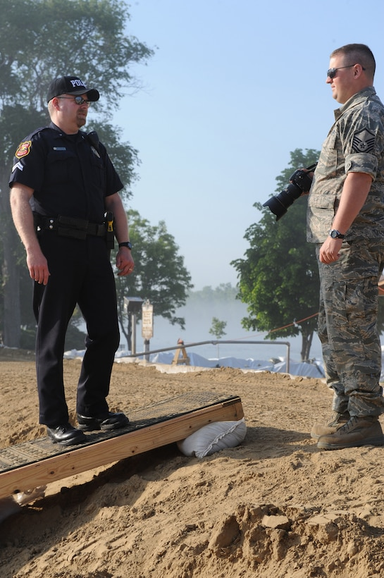 PIERRE, S.D. - Officer Eric Holmquist, Rapid City Police Department, talks with Master Sgt. Chris Stewart, a photographer with the 114th Fighter Wing public affairs, on a levee in Pierre, June 6, 2011. In addition to civilian authorities, South Dakota National Guard Airmen and Soldiers are conducting levee security and surveillance of the flooded Missouri River. (SDNG photo by Spc. Manda Walters) (RELEASED)