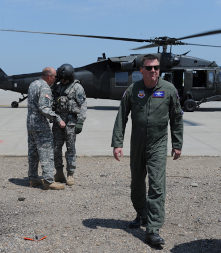 PIERRE, S.D. - South Dakota Air National Guard Col. Al Bolton (right), Director of Intelligence for the S.D. National Guard joint staff, returns from a survey of the Missouri River from a UH-60 Black Hawk, as aircrew members (left) discuss the follow-on mission, June 6, 2011. The S.D. National Guard response in Pierre and other cities along the Missouri River is a direct result of record snowfall in Montana that is begun to melt, along with heavy rainfall in eastern Wyoming, Montana and the western Dakotas. (SDNG photo by Manda Walters) (RELEASED)