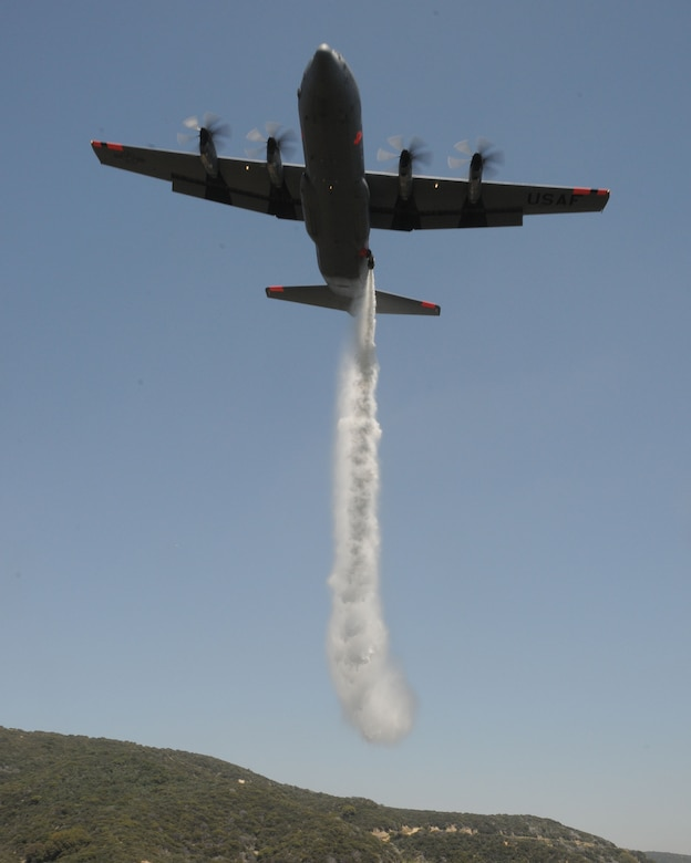 A C-130J from the 146th Airlift Wing, California Air National Guard, drops water over the Angeles Forest during Modular Airborne Firefighting System (MAFFS) training held June 7, 2011. The aircrews follow a U.S. Forest Service lead plane and demonstrate proficiency by dropping over a designated area. (Photo by Master Sgt. Dave Buttner)