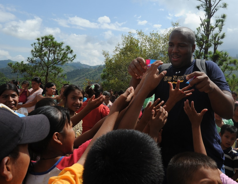 Petty Officer 2nd Class Corey Johnson, from Joint Task Force-Bravo, hands out candy to children June 11, 2011, at an isolated village near Comayagua, Honduras. More than 120 JTF-B members from Soto Cano Air Base, Honduras, hiked two miles up steep terrain to deliver food to people living in the town. All ranks of JTF-Bravo members chipped in nearly $1,700 for the food. (U.S. Air Force photo/Tech. Sgt. Matthew McGovern)