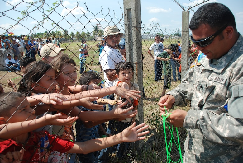 Sergeant Ernie Martinez, 1st Battalion, 228th Aviation Regiment, hands out ribbon to children at an air show June 12, 2011, at Colonel Armando Escalon Espinal Air Base, Honduras.  This annual event drew more than 10,000 people, raised money for a local civilian hospital and gave the opportunity for U.S. military members interact with the local community. Soto Cano AB, Honduras.