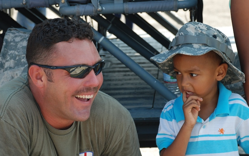 Chief Warrant Officer Brian Hayes shares a smile with a local child during the San Pedro Sula Air Show June 12, 2011, Honduras. Warrant Officer Hayes is from the 1st Battalion, 228th Aviation Regiment, Soto Cano Air Base, Honduras.