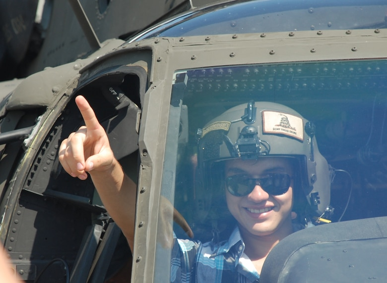 An air show participant sits in the pilot seat of a UH-60L Blackhawk June 12, 2011, at Colonel Armando Escalon Espinal Air Base, Honduras. This annual event drew more than 10,000 people, raised money for a local civilian hospital and highlights the dynamic relationship U.S. and Honduran Armed Forces share.
