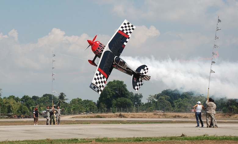 Aerial stunt performer Patty Wagstaff cuts ribbon while flying inverted as Honduran military, U.S. military and civilians assist at an air show June 12, 2011, at Colonel Armando Escalon Espinal Air Base, Honduras.  This annual event drew more than 10,000 spectators, raised money for a local civilian hospital and bolstered friendships between the military and civilian aviation community of the U.S. and Honduras.