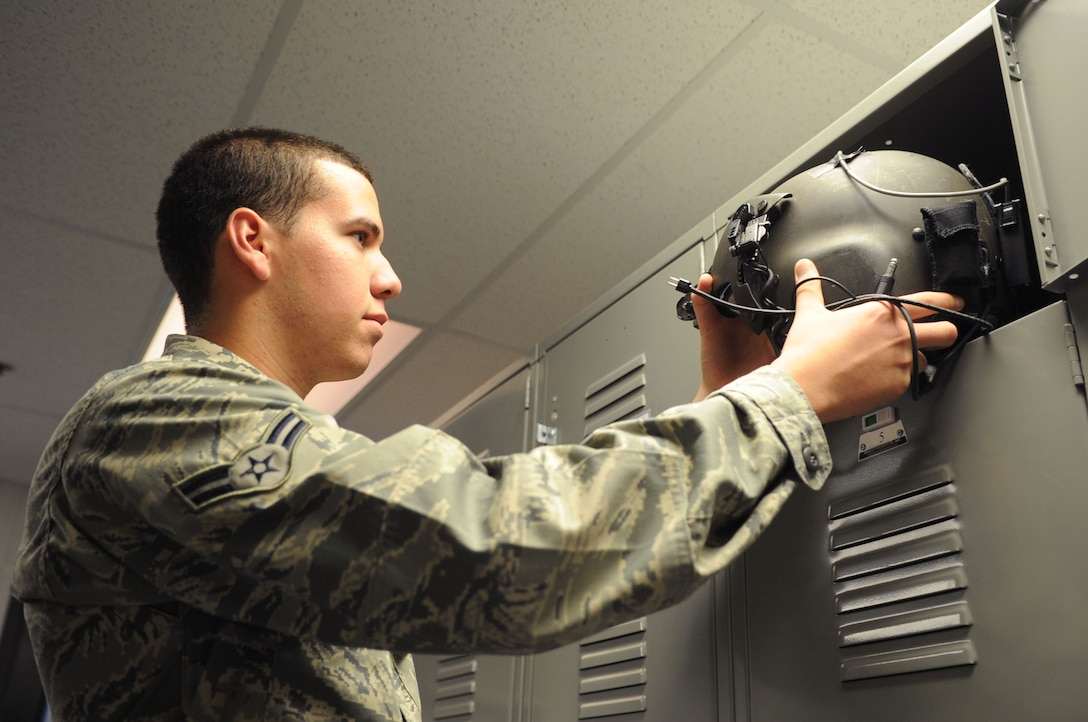 Airman 1st Class Richard Rodriguez, 811th Operation Support Squadron aircrew flight equipment technician, stows a flight helmet in a pilot's locker after he inspected it for function and servicability.  AFE inspects and maintains other equipment as well, to include night-vision goggles, life preservers and survival kits. (U.S. Air Force photo by Senior Airman Torey Griffith)(released)