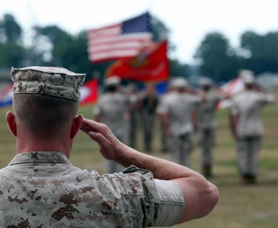 A Marine with 1st Battalion, 8th Marine Regiment, 2nd Marine Division, salutes his unit colors and the American flag during a change of command ceremony, June 17, 2011, aboard Marine Corps Base Camp Lejeune, N.C. Lt. Col. Daniel T. Canfield Jr. relinquished his duties as commanding officer of 1st Battalion, 8th Marine Regiment, 2nd Marine Division, to Lt. Col. Kevin C. Trimble.