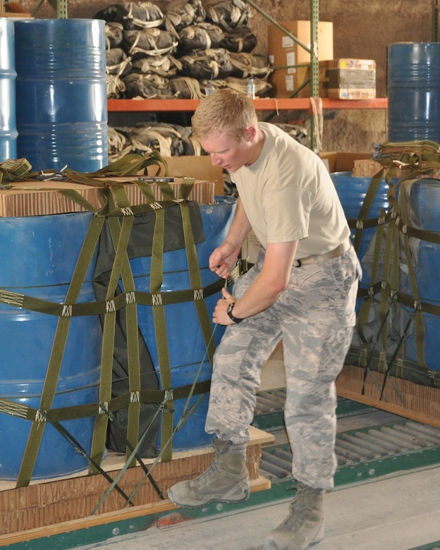 Cadet 1st Class Jordan Wittman, United States Air Force Academy Cadet Squadron 30, pulls tightly on straps to ensure the cargo bundle is securely fastened to the pallet while working with U.S. Army Riggers June 18 at a deployed air base. Cadet Wittman is in Southwest Asia taking part in Deployed Ops, a summer program which sends Academy cadets to deployed locations. (U.S. Air Force photo/Cadet 1st Class Shaina Thompson)