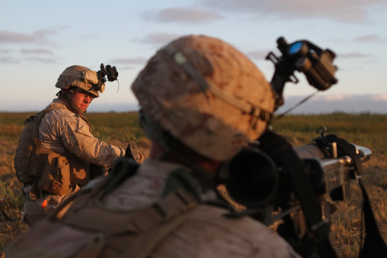 Cpl. William G. Stickney watches a Marine simulate launching a rocket during night raid rehearsals here June 19. Stickney, a 22-year-old Roanoke, Va., native, serves as a machine gun team leader with Company L, one of three rifle companies in Battalion Landing Team 3/1, the ground-combat element for the 11th Marine Expeditionary Unit. The unit recently began its first full-scale exercise since becoming a complete Marine air-ground task force in May.