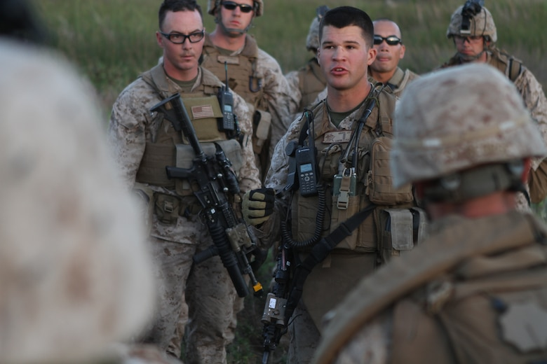 Platoon commander 2nd Lt. John P. Krudy debriefs Marines and sailors after night raid rehearsals here June 19. Krudy, a 24-year-old Vienna, Mich., native, serves with Company L, one of three rifles companies in Battalion Landing Team 3/1, the ground-combat element for the 11th Marine Expeditionary Unit. The unit recently began its first full-scale exercise since becoming a complete Marine air-ground task force in May.
