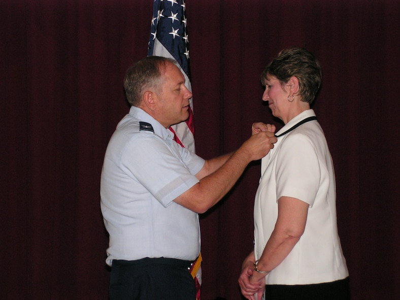 Col. Kevin Wooton, 67th Network Warfare Wing commander, gives Deborah Wilson, 67th NWW Wing Plans deputy, a pin in honor of 30 years of federal service. Ms. Wilson started her career as a typist at Randolph Air Force Base, Texas. (courtesy photo)