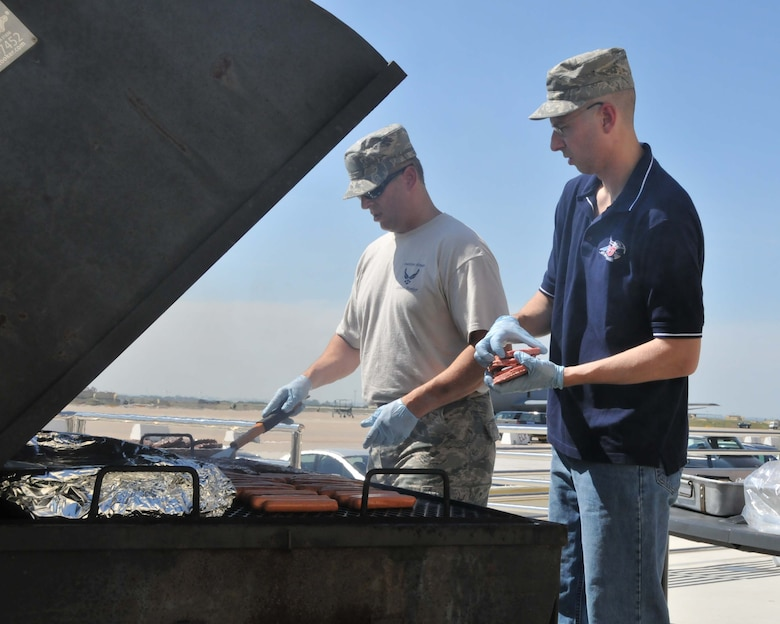 """Command Chief Master Sgt. Joseph A. Parlato (left) and 1st Sgt./Senior Master Sgt. Brian C. Boyle, 313th Air Expeditionary Wing prepare hamburgers, hot dogs, and baked beans for esprit-de-corps builder """"burger burn"""" on June 16, 2011 in Western Europe. (U.S. Air Force Photo/Capt John P. Capra)"""