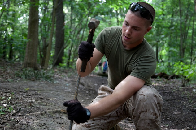 Lance Cpl. Erik S. Potts pounds in a length of rebar into a log to hold it into place for one of the drainage ditches at Forest Park in St. Louis, June 20. The Marines and Boy Scouts worked together to show their appreciation to the community by fixing the trail. Marine Week provides an opportunity to increase public awareness of the Marine Corps' value to our nation's defense and to preserve and mature the Corps' relationship with the American people.::r::::n::