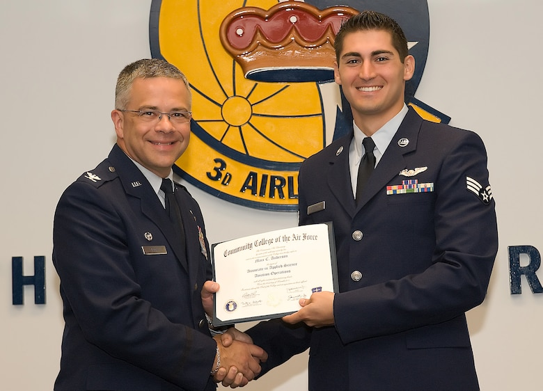 Col. Randal L. Bright, 512th Airlift Wing commander, presents Senior Airman Marc Anderson, 326th Airlift Squadron, with an associate in applied science degree June 12 during a Community College of the Air Force graduation ceremony on base. Airman Anderson is a loadmaster who received his degree in Aviation Operations. (U.S. Air Force photo by Steve Kotecki/Released)
