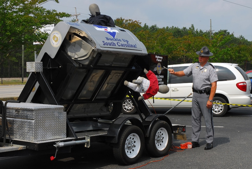 South Carolina Highway Patrol Lance Corporal Bob Beres demonstrates the roll-over crash simulator during a traffic safety event at Joint Base Charleston-Weapons Station June 15. The simulator, which uses crash dummies, demonstrates how individuals not wearing seat belts can be thrown from a vehicle during a roll-over crash at only 12 to 15 mph. (U.S. Navy photo/Machinist's Mate 3rd Class Brannon Deugan)