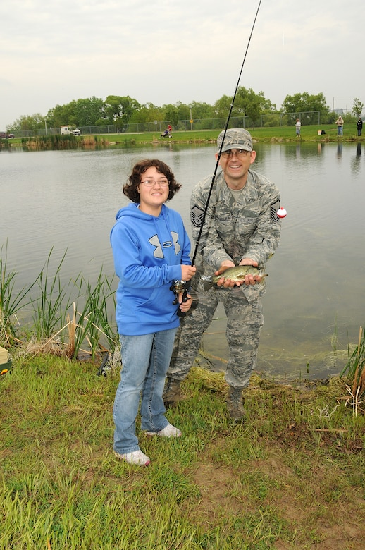 """Rachel, (left) a senior at Lincoln Northstar High school enrolled in the Functional Community Reference program, and her fishing buddy Master Sgt. Aaron Aulner, 155th Air Refueling Wing Prime Ribs manager, show off a fish they caught on May 20, 2011 during the annual """"Gators Gone Fishin"""". This is the second year Rachel and Master Sgt. Aulner paired together to catch fish and enjoy the event. (Nebraska Air National Guard photo by Senior Master Sgt. Lee Straube)"""