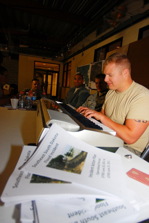 DAKOTA DUNES, S.D. - Senior Airman Zach Gunn,114th Fighter Wing, plays piano and sings songs to help pass the time for the Soldiers and Airmen who would normally be performing levee patrols and quick reaction force duties while taking shelter from a thunderstorm June 20, 2011, in the Dakota Dunes Liberty Bank building. The storm dropped nearly three inches of rain on the already saturated neighborhoods, while the Missouri River continues to rise nearby. (photo by Tech. Sgt. Quinton Young)(RELEASED)